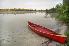 Canoa rossa tirata sul lago Fotografie Stock