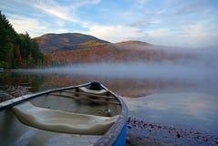 Canoa sulla spiaggia della riva del lago Fotografia Stock