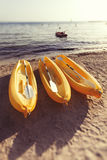Canoa três amarela plástica na praia no mar verão Fotos de Stock