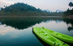 Canoa verde no lago no tempo do nascer do sol Fotografia de Stock