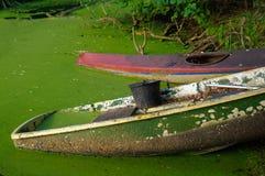 Canoa vieja y una bota de madera en tierra la charca con el cubo en él fotografía de archivo libre de regalías