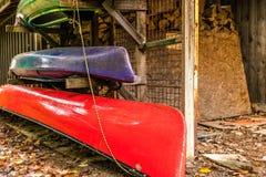 Canoa y kajak brillantemente coloreados, almacenados en la cabaña cerca del w imágenes de archivo libres de regalías