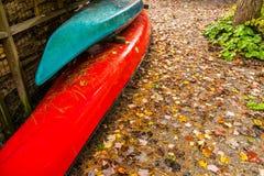 Canoa y kajak brillantemente coloreados, almacenados en la cabaña cerca del w fotografía de archivo