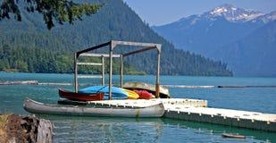 Canoas coloridas en el muelle del lago mountain Imagen de archivo libre de regalías