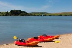 Canoas coloridas pelo lago com céu azul Fotografia de Stock Royalty Free