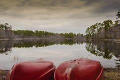 Canoas por el lado y la reflexión del lago Foto de archivo libre de regalías