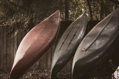 Canoas viejas que se inclinan en una cerca en verano Foto de archivo