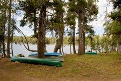 Canoas vueltas hacia arriba por la orilla del lago Fotos de archivo libres de regalías