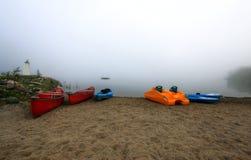 Canoas y kajak en niebla fotos de archivo