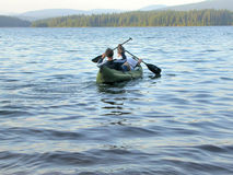 Canoe. A father and son set sail on a canoe ride out into Timothy Lake Stock Photography