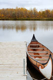 Canoe. A canoe docked and floating on the river, shot on a cloudy day Stock Image