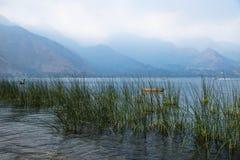 Canoe atrás do junco com as montanhas enevoadas em Lago Atitlan, San Juan la Laguna, Guatemala, América Central foto de stock royalty free
