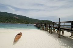 Canoe on a beach. Canoe on a tropical beach with jetty in the background, this is taken in a remote island in Malaysia Royalty Free Stock Photo