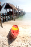 Canoe on the beach near traditional wooden bridge. Royalty Free Stock Photography