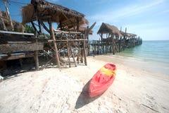 Canoe on the beach near traditional wooden bridge. Stock Image