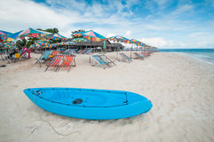 Canoe boat on the beach with seat and umbrella Royalty Free Stock Photo