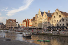 Canoe and boats in river Leie in medieval centre in belgian town Royalty Free Stock Photos