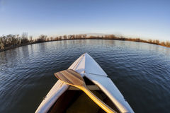 Canoe bow and paddle. Bow of white decked canoe with wooden paddle on a calm lake in Colorado - a fish eye lens perspective royalty free stock photography