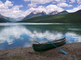 Canoe at Bowman Lake. Canoe beached at the shore of Bowman lake waiting to be taken out. Green lake with beautiful mountains and sky in the background Stock Images