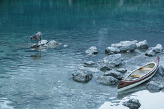 Canoe on calm blue lake and dog, Aibsee, Germany Royalty Free Stock Photos