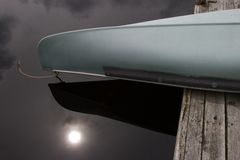Canoe Close-Up. Close-up of a canoe, overhanging a wood dock, with the sun reflecting in the dark water Royalty Free Stock Images