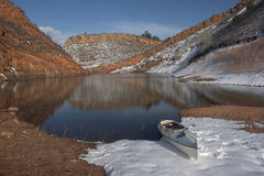 Canoe on Colorado mountain lake. Decked expedition canoe on Colorado mountain lake (Horestooth Reservoir near Fort Collins) in early spring with red sandstone stock photography