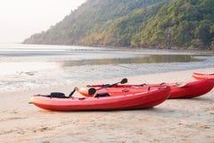 Canoe com pá e revestimento de vida na praia no por do sol fotos de stock royalty free