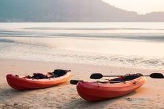 Canoe com pá e revestimento de vida na praia no por do sol foto de stock