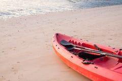 Canoe com pá e revestimento de vida na praia no por do sol foto de stock royalty free