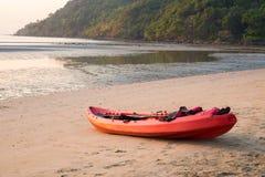 Canoe com pá e revestimento de vida na praia no por do sol fotografia de stock royalty free