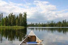 Canoe con l'attrezzatura per la pesca che si dirige fuori sul lago del Nord Immagine Stock