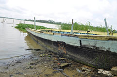 CANOE A COUNTERFEIT MATERIALS. Pirogue in disrepair near water because of its counterfeit materials were used in its manufacture. daily real danger he Stock Photography