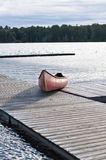 Canoe on Dock - Muskoka, Ontario, Canada. A red canoe is pulled up onto a dock on a lake in Muskoka, Ontario, Canada Stock Images