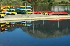 Canoe Dock and Rentals. Colorful rental canoes are reflected in the water around the dock Royalty Free Stock Photography