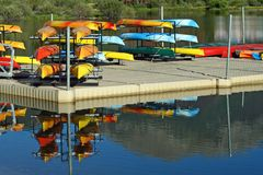 Canoe Dock and Rentals. Colorful rental canoes are reflected in the water around the dock Stock Images