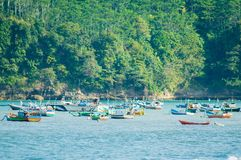 Canoe e pescherecci sul mare contro il contesto delle foreste verdi immagini stock