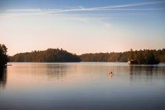 Canoe en el lago tranquilo José, Muskoka, en la salida del sol fotografía de archivo