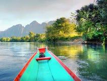 Canoe en un río rodeado con las montañas asombrosas foto de archivo libre de regalías