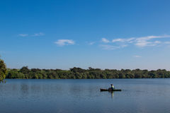 Canoe fisherman. Blue sky and lake Royalty Free Stock Photos