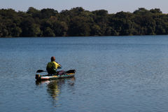Canoe fisherman. Blue sky and lake Stock Images