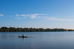 Canoe fisherman. Blue sky and lake Royalty Free Stock Images