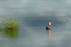 Canoe fishing. Fisherman in the canoe with fog - River Amazon Stock Images