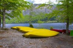Canoe gialle in una fila sulla spiaggia del lago Bohinj Immagini Stock Libere da Diritti