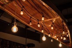 Canoe hanging from ceiling with string lights stock photos