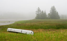 Canoe on inlet in fog. A view of a small white canoe on the shore of a Maine tidewater inlet in morning fog stock image