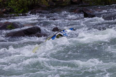 Canoe Jammed River Rapids. Canoe doubles jammed by water energy power in river rapids rocks Stock Photo