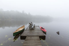 Canoe and kayak tied to a dock on a misty lake - Ontario, Canada Royalty Free Stock Images