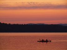 Canoe at the lake. Canoe gliding through the lake waters at the sunset Stock Image