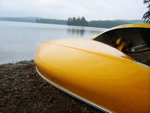Canoe by lake. Canoes by the lake painted bright yellow with pretty landscape background stock images