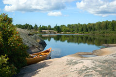 Canoe Beside Lake. Cedar strip canoe sitting in water next to rocky shoreline royalty free stock photos